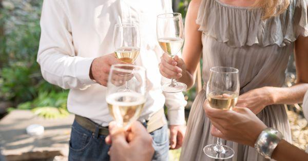 Ludzie wznoszący toast białym winem