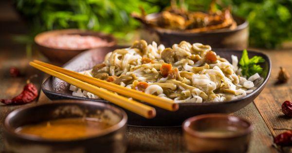 Pad thai z kurczakiem w brązowej misce z pałeczkami