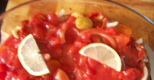 Ryba zapiekana po hiszpańsku - polewamy pozostałymi pomidorami a na wierzchu układamy plaster cytryny
