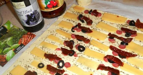 Ślimaczki z francuskiego ciasta - Pokrojone w paski ciasto posypać ziołami i obłożyć różnościami.