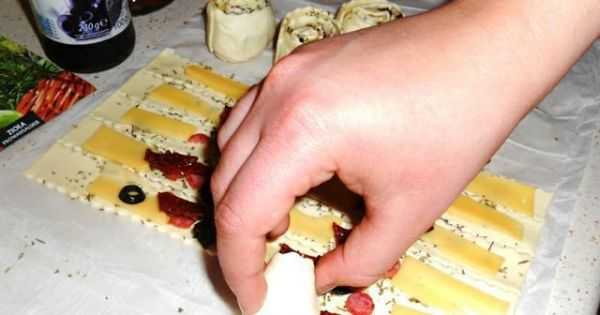 Ślimaczki z francuskiego ciasta - Obłożone paski ciasta zwinąć w ruloniki.