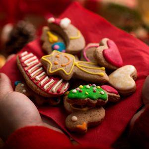Damskie dłonie ze świątecznymi, ozdobnymi ciasteczkami, w tle ciepłe światło i świeczki
