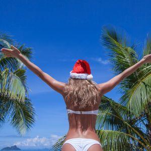 Kobieta w czapce Mikołaja na plaży pod palmami