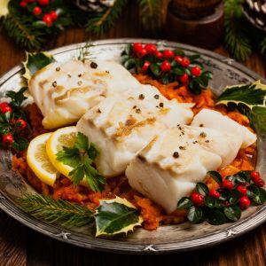 Ryba po grecku na ozdobnym talerzu ze świątecznymi dekoracjami
